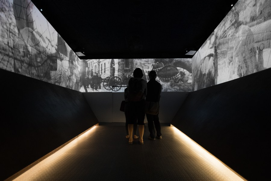 Colour photo. Three people stand in a dark room, surrounded by projected images on a wall.