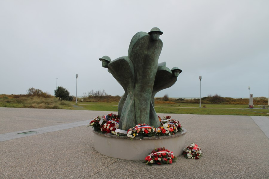 Colour photo. Remembrance and Renewal sculpture, with wreaths at the bottom.