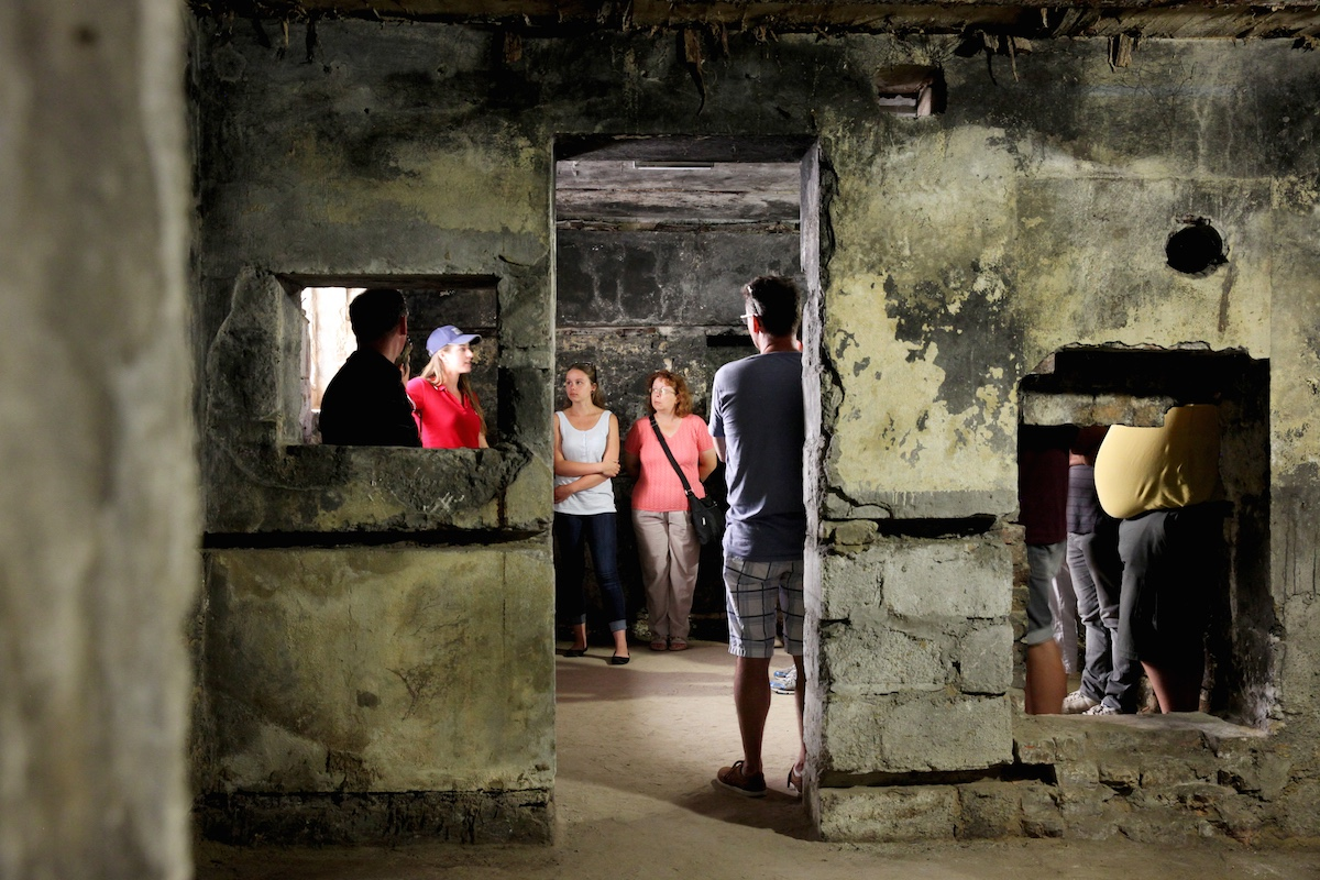 Colour photo. A guide gives a tour inside a restored German bunker.