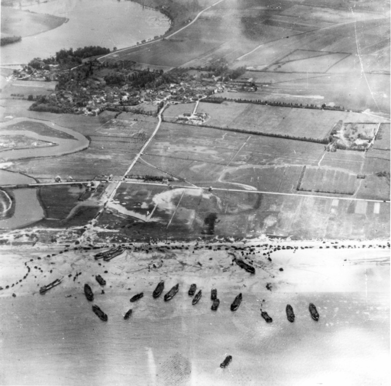 """Blake and white photograph. """"Mike Red"""" Beach on 6 June 1944. Landing craft run up on the beach to unload their cargoes of men, vehicles and supplies. The present-day site of the Juno Beach Centre is just to the left of the photograph across the Seulles River. The town in the background is Graye-sur-Mer. Source: Courtesy of the Juno Beach Centre Association"""