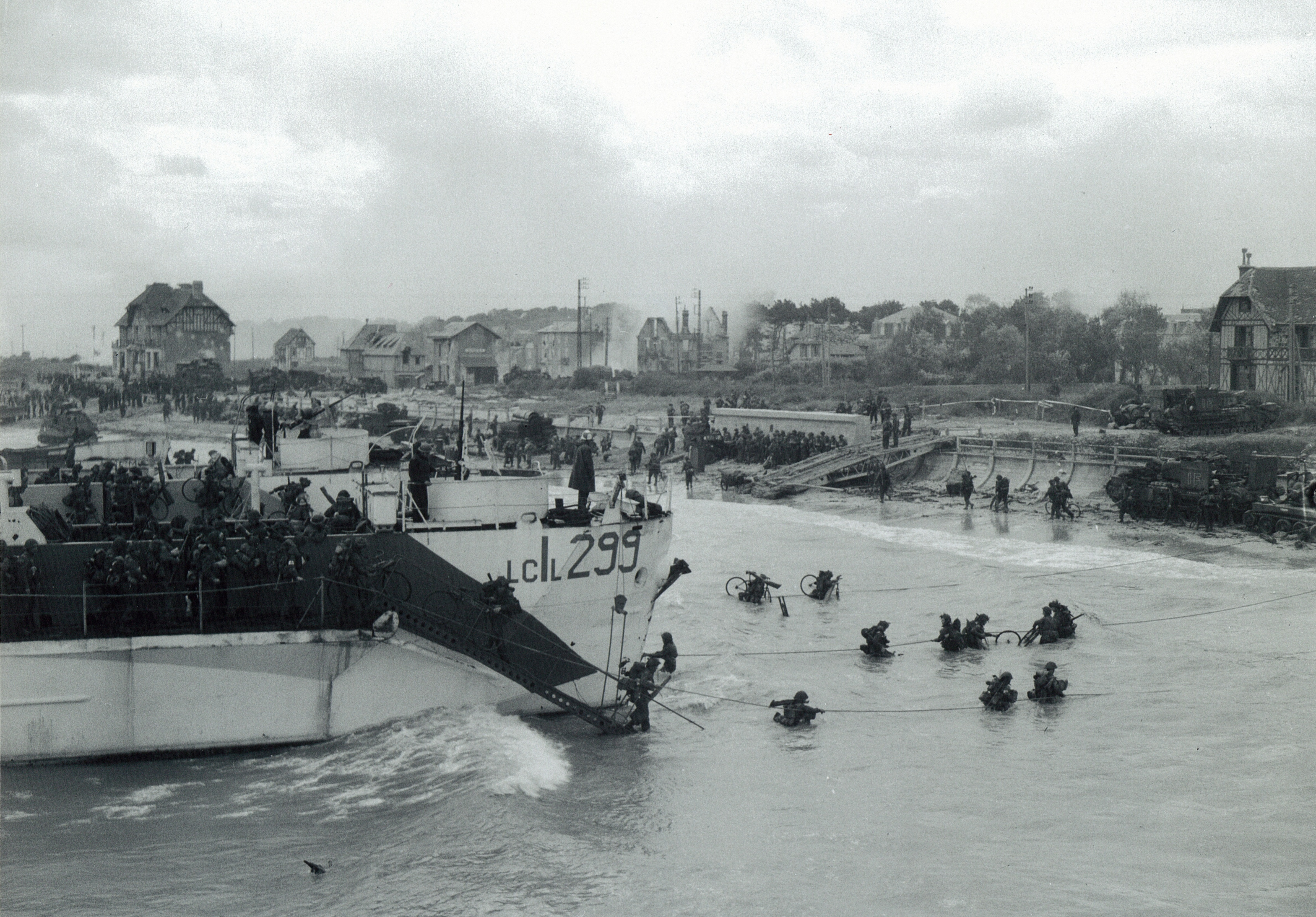 Black and white photograph. Troops of the 9th Canadian Infantry Brigade (Stormont, Dundas, and Glengarry Highlanders) going ashore from LCI (L) 299 [Landing Craft Infantry], Bernières-sur-mer, Normandy, France, 6 June 1944.  Source: Lieut. Gilbert A. Milne / DND / Library and Archives Canada / PA-131506 / Courtesy of the Juno Beach Centre Association