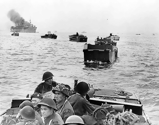 Black and white photograph. Infantrymen of The Royal Winnipeg Rifles in Landing Craft Assault (LCAs) enroute to land at Courseulles-sur-Mer, France, 6 June 1944. Source: Canada. Dept. of National Defence / Library and Archives Canada / PA-132651 / Courtesy of the Juno Beach Centre Association
