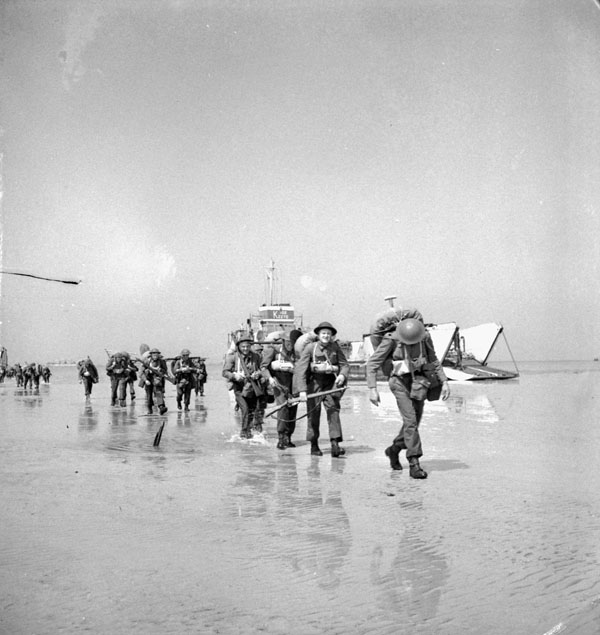 Black and white photograph. Unidentified Canadian soldiers landing on Juno Beach, Courseulles-sur-Mer, France, 6 June 1944.  Source: Lieut. Ken Bell / Canada. Dept. of National Defence / Library and Archives Canada / PA-132655 / Courtesy of the Juno Beach Centre Association