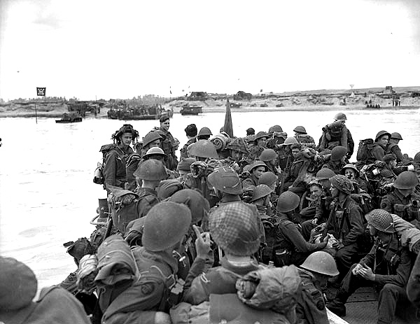 "Black and white photograph. Personnel of Royal Canadian Navy Beach Commando ""W"" landing on Mike Beach, Juno sector of the Normandy beachhead, France, 8 July 1944.  Source: Lt Richard Graham Arless / Canada. Dept. of National Defence / Library and Archives Canada / PA-182953 / Courtesy of the Juno Beach Centre Association"