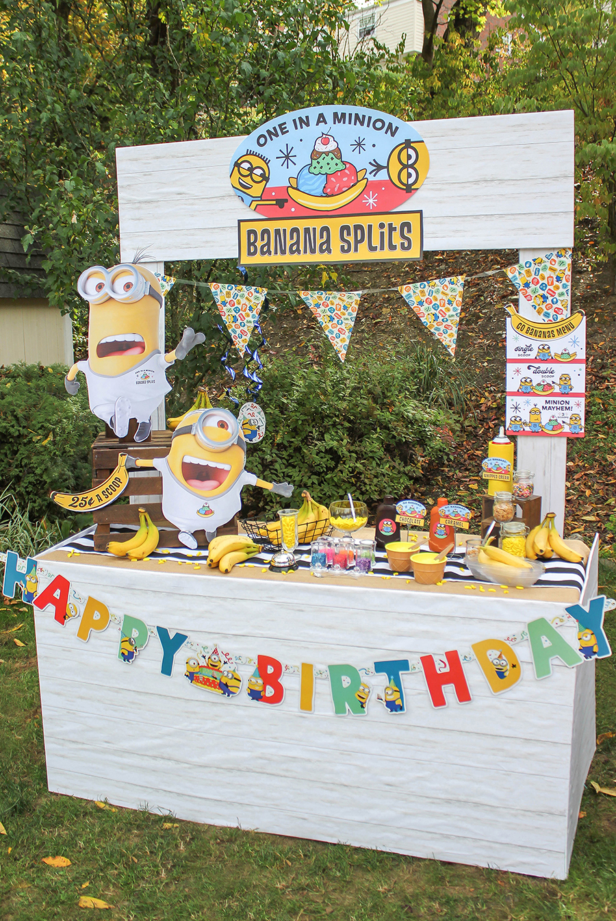 Minions Birthday Party, minions, kids party, kids birthday, ice cream party, banana split, one in a minion, banana split party, one in a minion banana splits, banana, minion, here's the scoop, DIY ice cream bar, DIY banana split bar, Minions party ideas, minions food ideas, Minions birthday party decorations, Minions birthday party theme, Minions birthday party ideas, Just Add Confetti, banana split stand, backyard birthday party, outdoor party, banana stand, ice cream stand