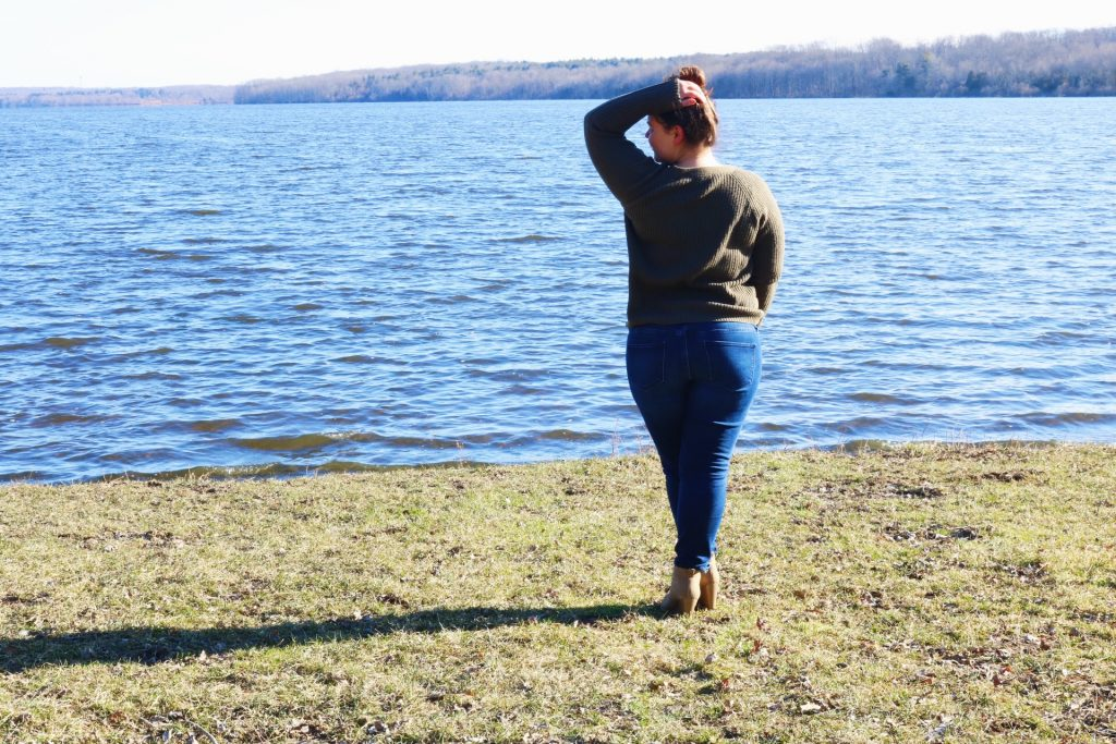 me standing facing the lake with my arm raised and head turned slightly towards my raised arm.
