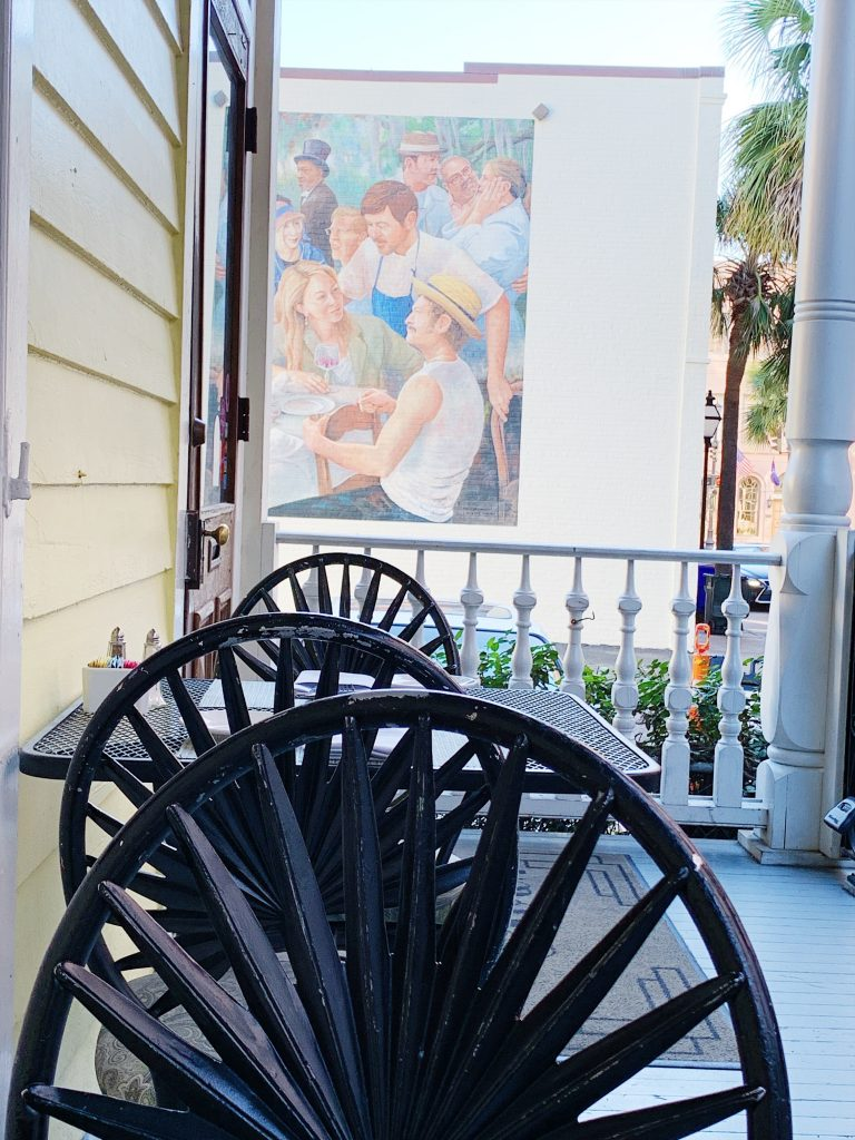 a photo of the upper porch of poogan's porch. There is a chair in front of me and then a table for two behind that chair. There is a beautiful mural of people on the building next to Poogan's Porch in direct line of sight behind the table for two.