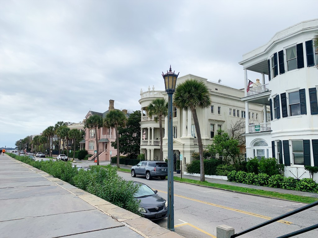 a photo of the row of historic homes that line the battery strip of road by the water in charleston