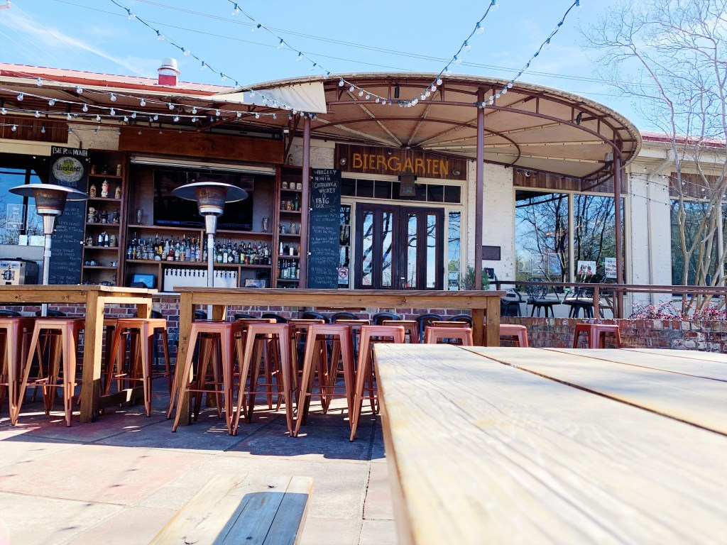 a photo of the outdoor patio area of the bay street biergarten. There is an outdoor bar with high top tables and stools as well as strings of outdoor lights draped from the bar area to the back of the patio area.