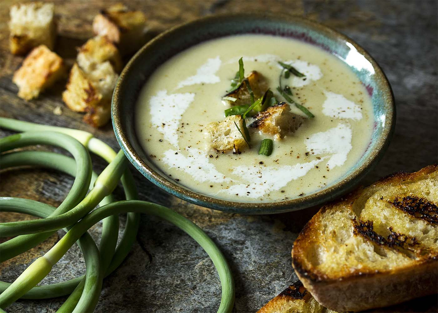 A bowl of cold garlic scape soup topped with garnishes. Grilled bread and garlic scapes scattered about.