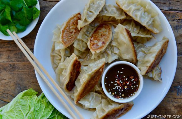 Pork Potstickers with Citrus-Soy Dipping Sauce on white plate with chopsticks next to bowl containing cilantro