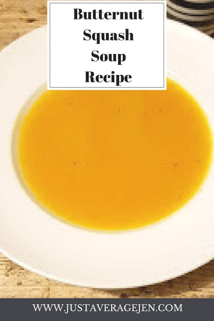 A white large rimmed bowl full of a smooth orange butternut squash soup