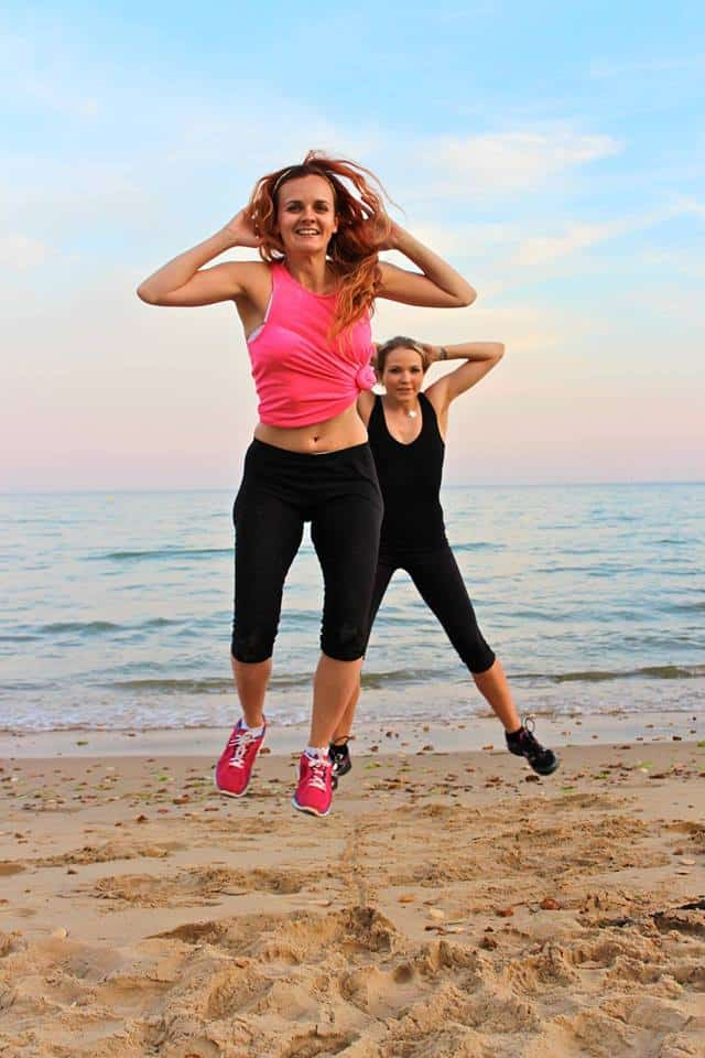 two ladies on the beach in the sun with the sea behind them jumping in the air, legs wide and hands behind their heads