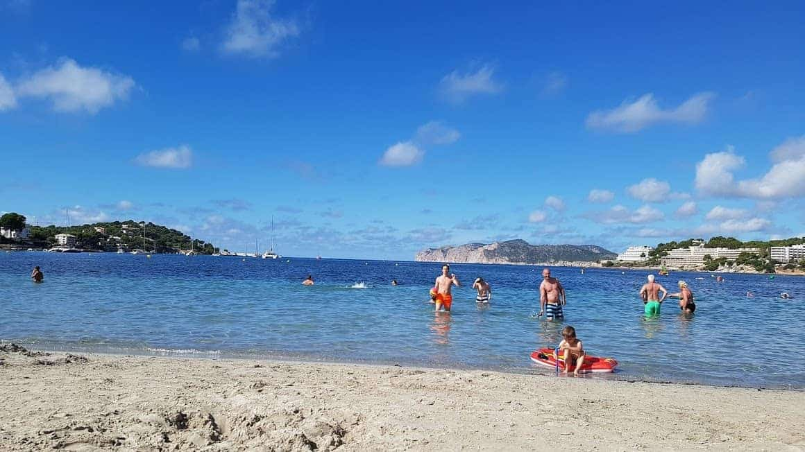 A sunny beach view showing blue sea and sand with people swimming at Santa Ponca