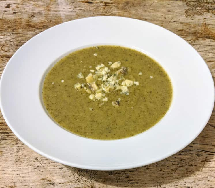 Bowl of green broccoli soup with stilton crumbled on top