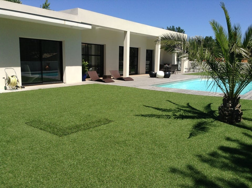 pool with grass outside a villa in the sun