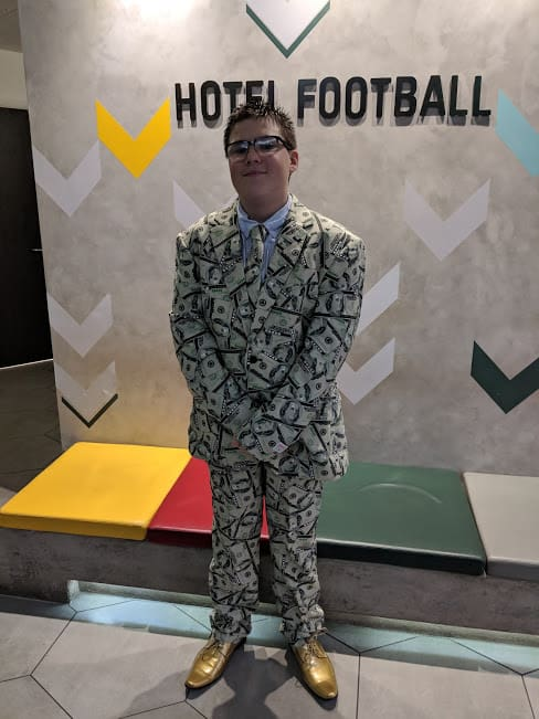 Ben in a suit covered in dollar bills
