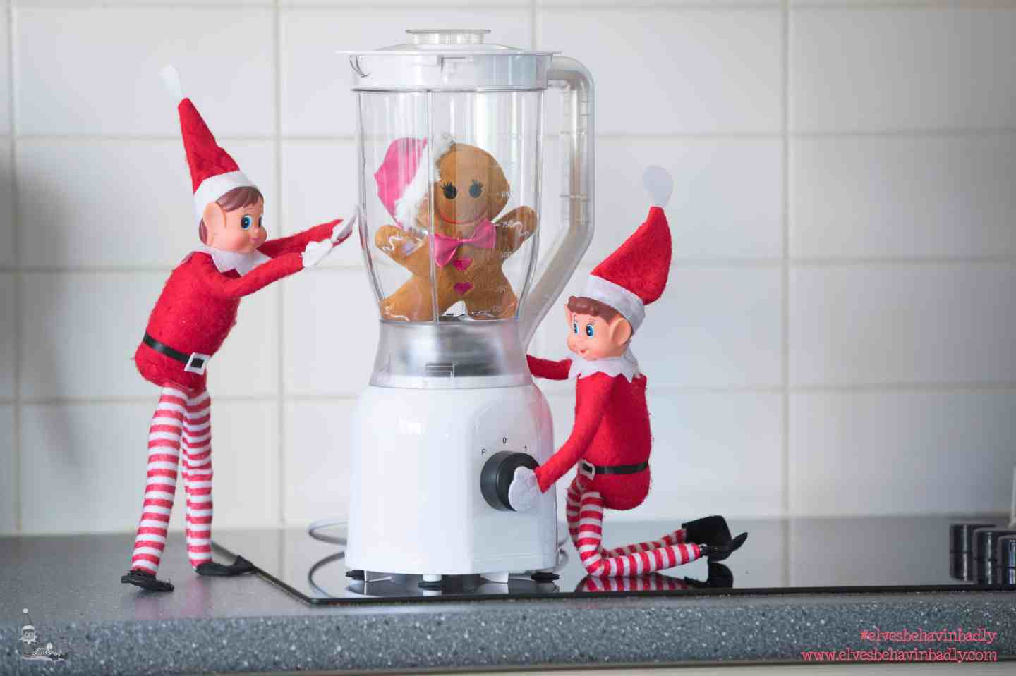 two elves with a gingerbread man in a blender!