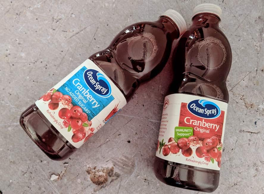 two bottles of ocean spray cranberry juice on grey background