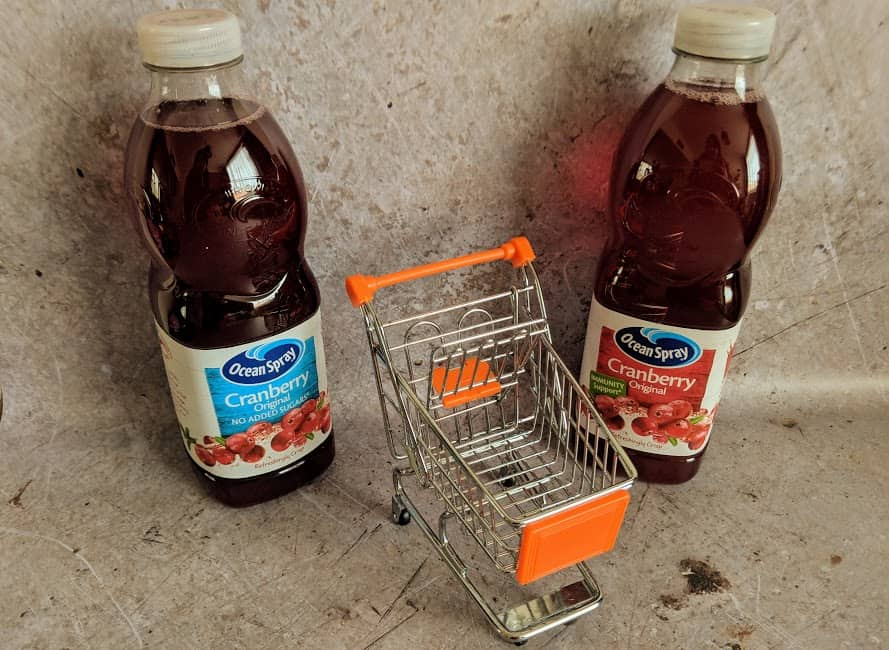 two bottles of cranberry juice and a mini shopping trolley