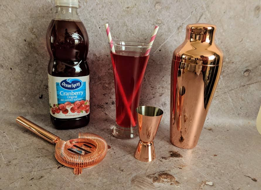cranberry juice with cocktail shaker and other cocktail items