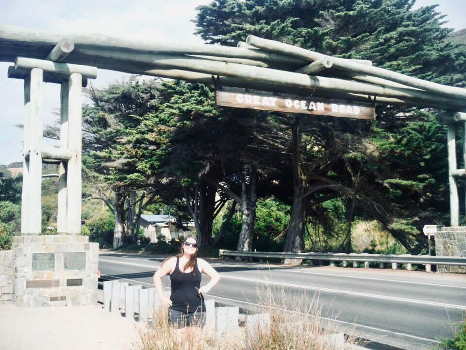 Standing underneath the Great Ocean Road Memorial Sign