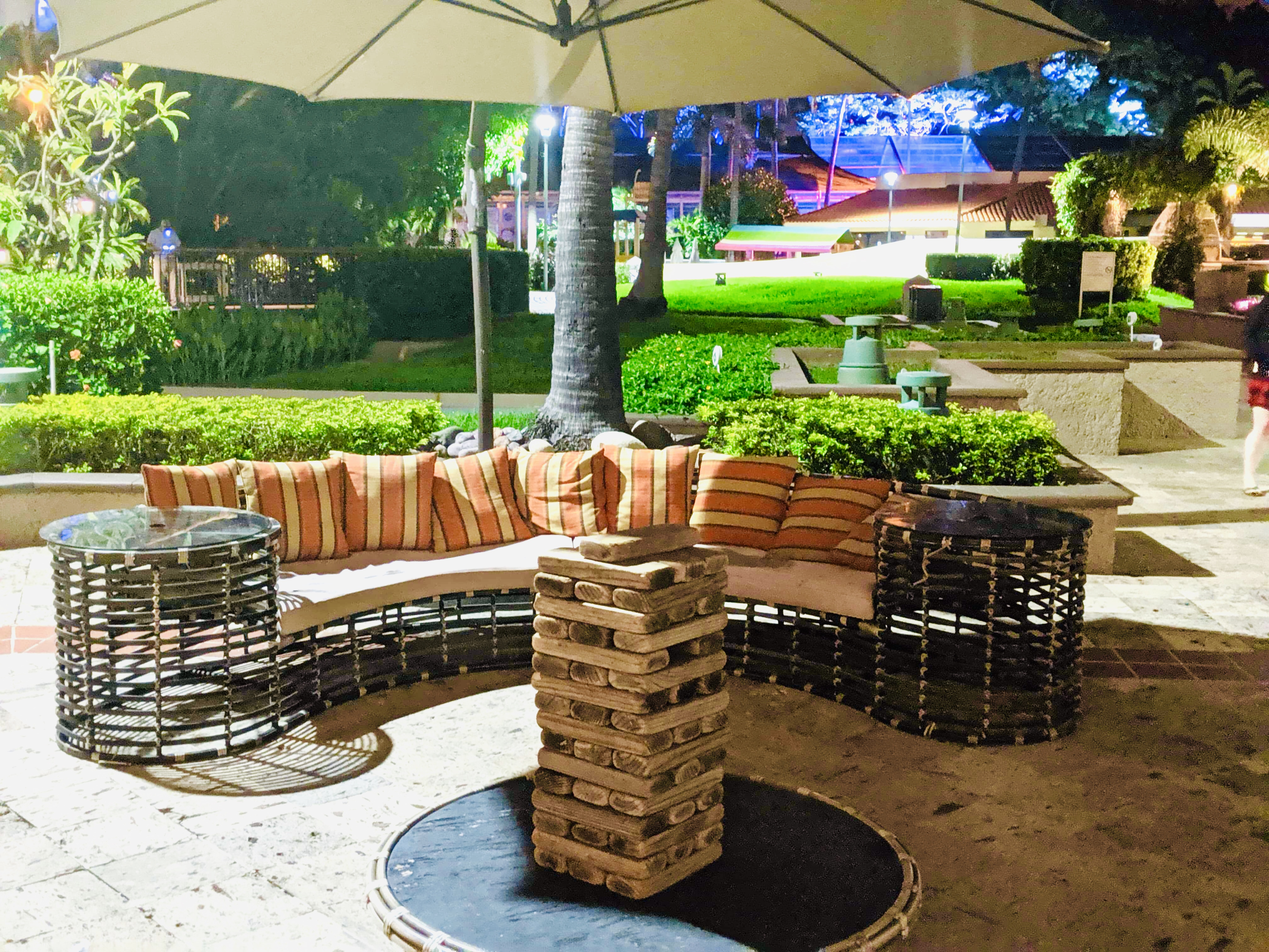 A seating area outside with a giant jenga game set up on a table