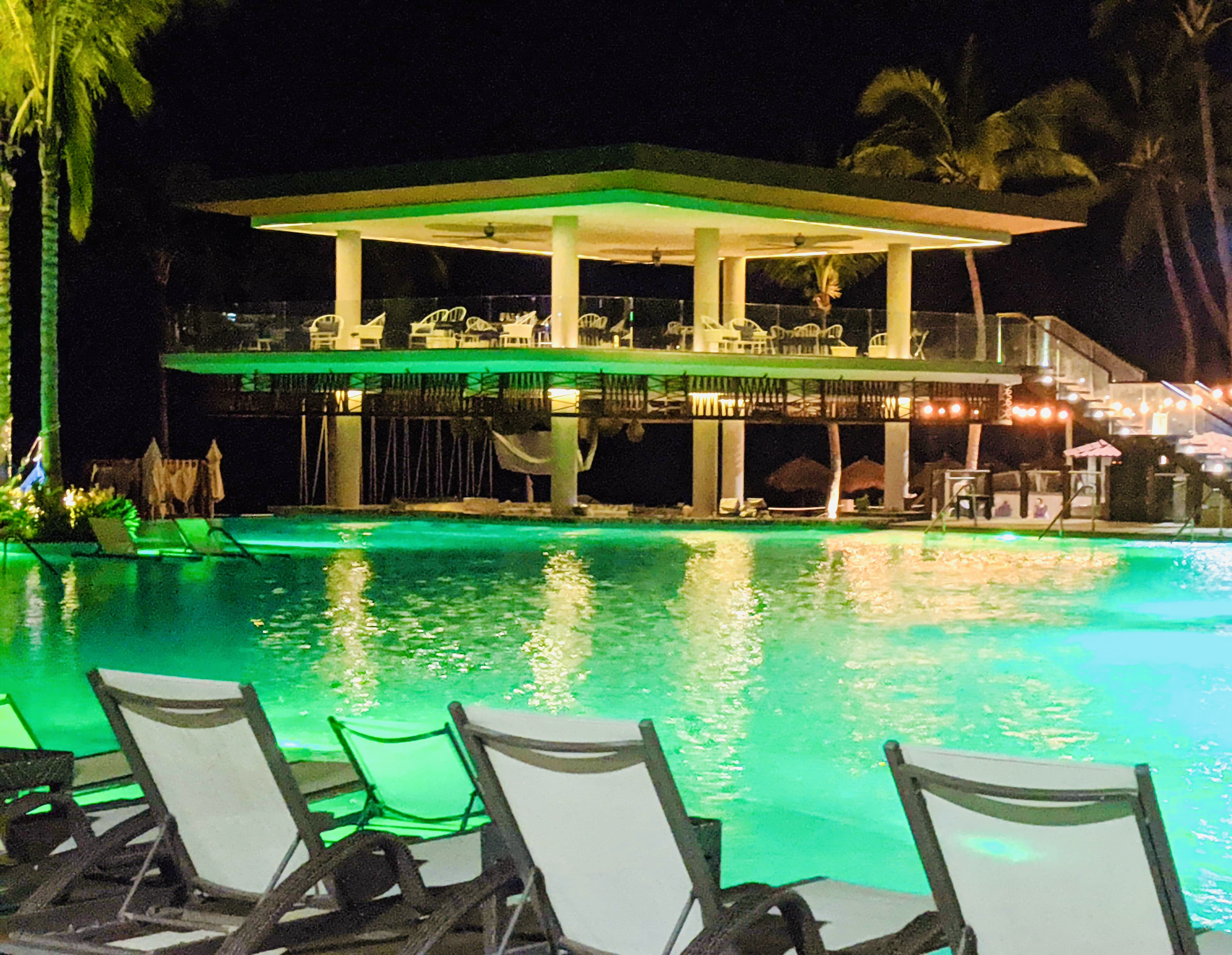 The pool area at night, looking over to the outdoor restaurant