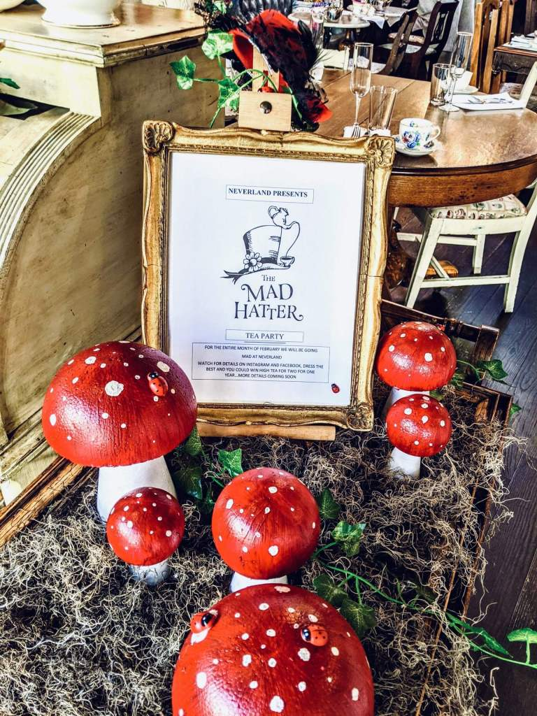 A front window display with fake mushrooms in grass