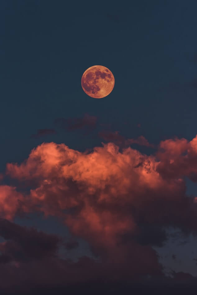 A red moon and clouds against a dark blue sky