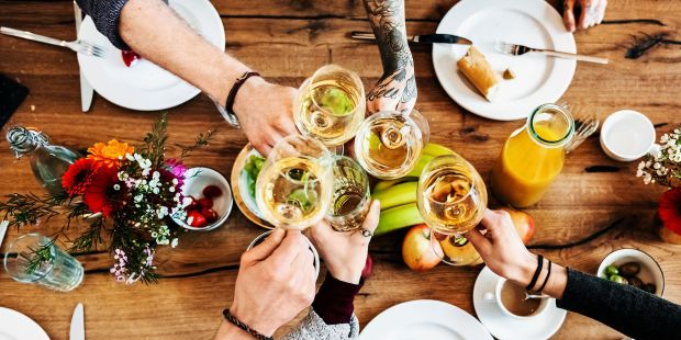 hands toasting wine glasses over a meal