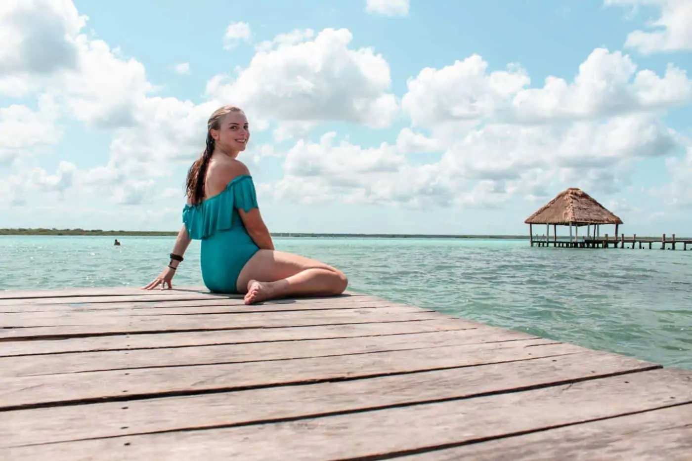 girl in bathing suit sitting on a dock