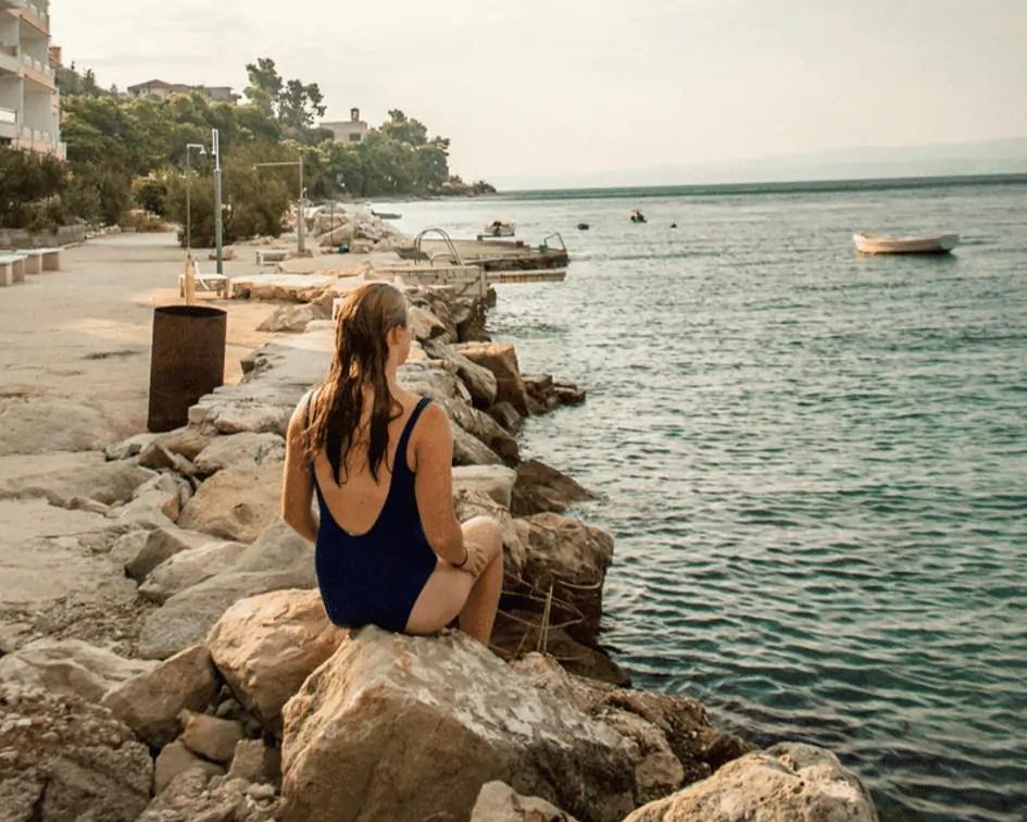 girl sitting on rocks overlooking the sea