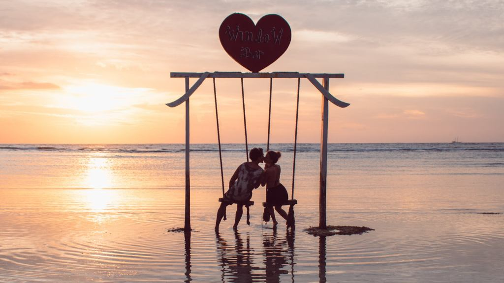 Couple kissing on swing in the ocean Gili Trawagan island Indonesia