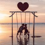 Couple kissing on swing in the ocean Gili Trawagan island Indonesia