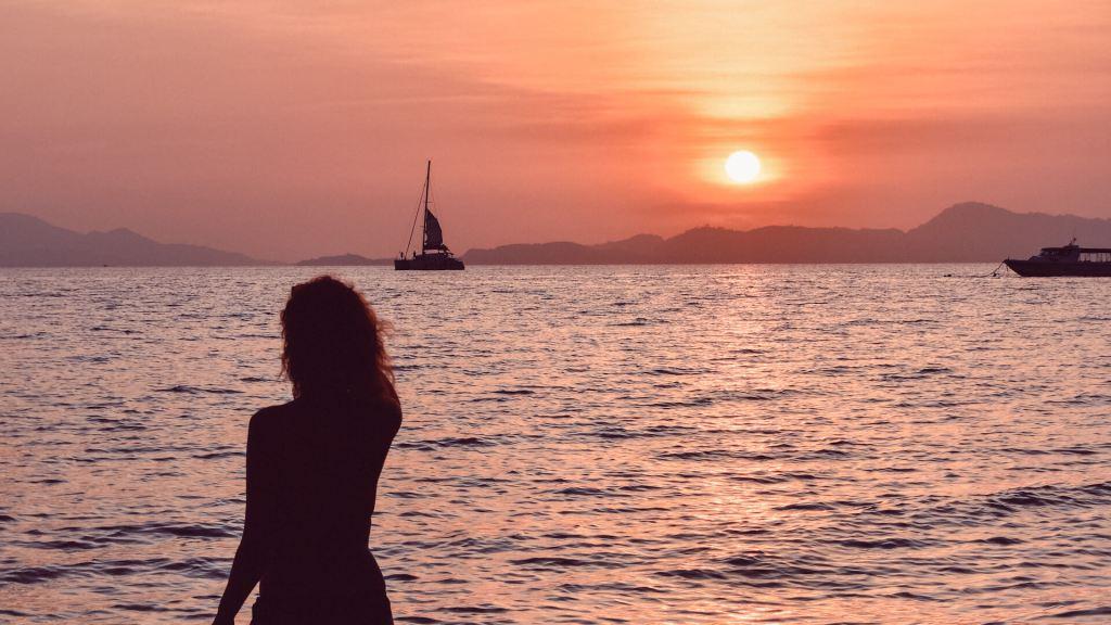 Girl in the sea at sunset on Yao Yai beach in Thailand