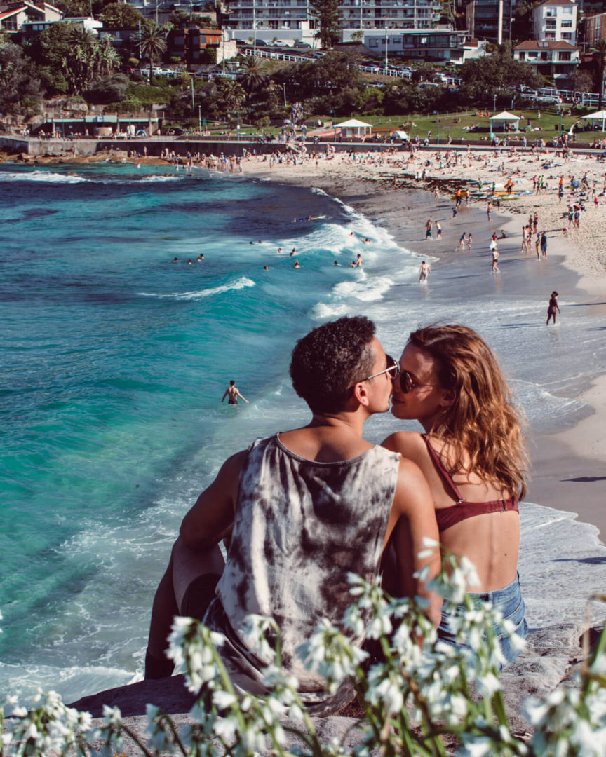 couple kissing on coogee beach rock overlooking the blue ocean