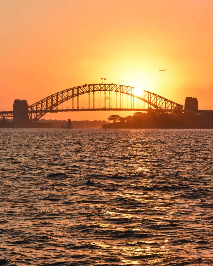A picture of Sydney Bridge at sunset, orange sky