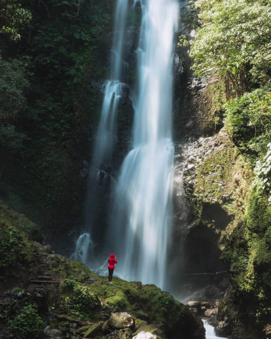 Women in red coat standing next to melanting waterfall
