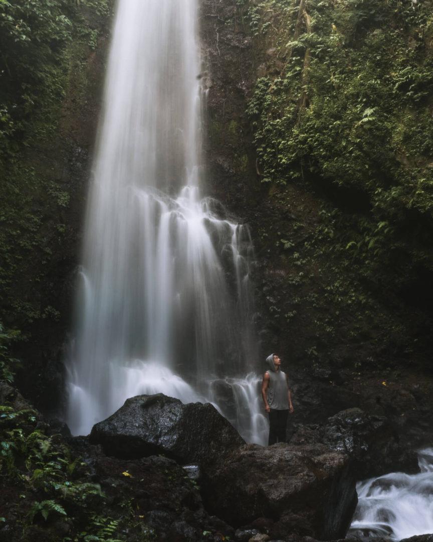 Man posing next to Lebuhan Kebo Waterfall Bali