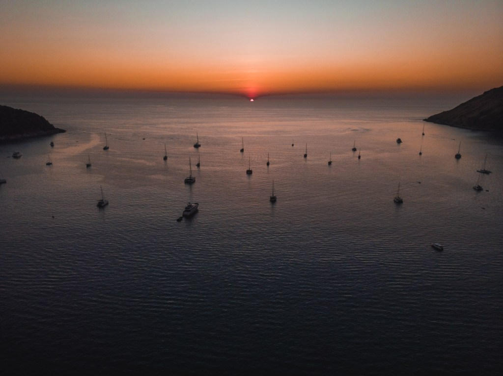 End of sunset over boats on Nai Harn ocean