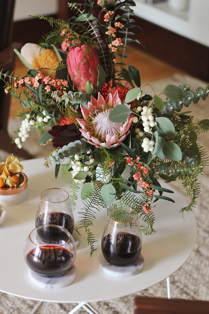 A Cozy Girls Night In | An eclectic November's arrangement made with Euphorbia, Snowberries, King Protea, Banksia, Pin Cushions, Safari Sunset Leucodendron, Coral Fern and a trio of Seeded, Baby and Silver Dollar Eucalyptus // JustineCelina.com