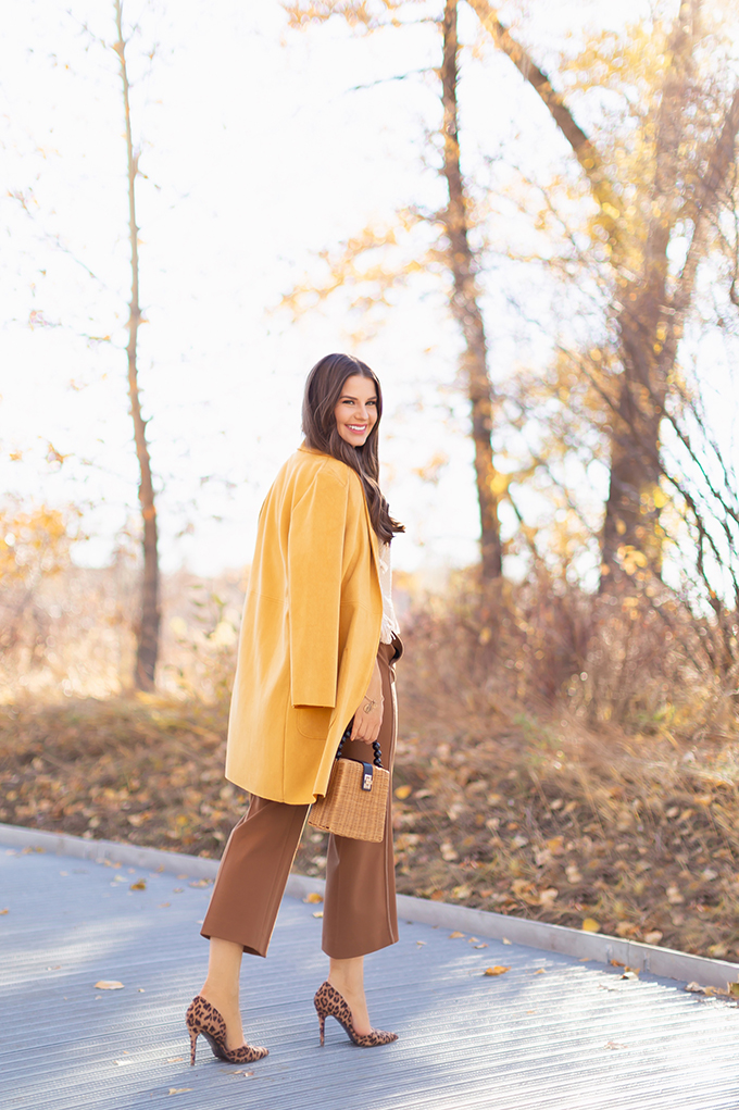 WORK WEAR | SPRING 2019 TRENDS AT THE OFFICE | How to Style Culottes for the Office | Brown 70's Style Culottes with a Mustard Faux Suede Jacket, Knit Fringe Hem Top, Natural Material Rattan Woven Box Bag and Leopard Print D'Orsay Heels | Spring 2019 Trends | Office Appropriate Spring Outfit Ideas // JustineCelina.com