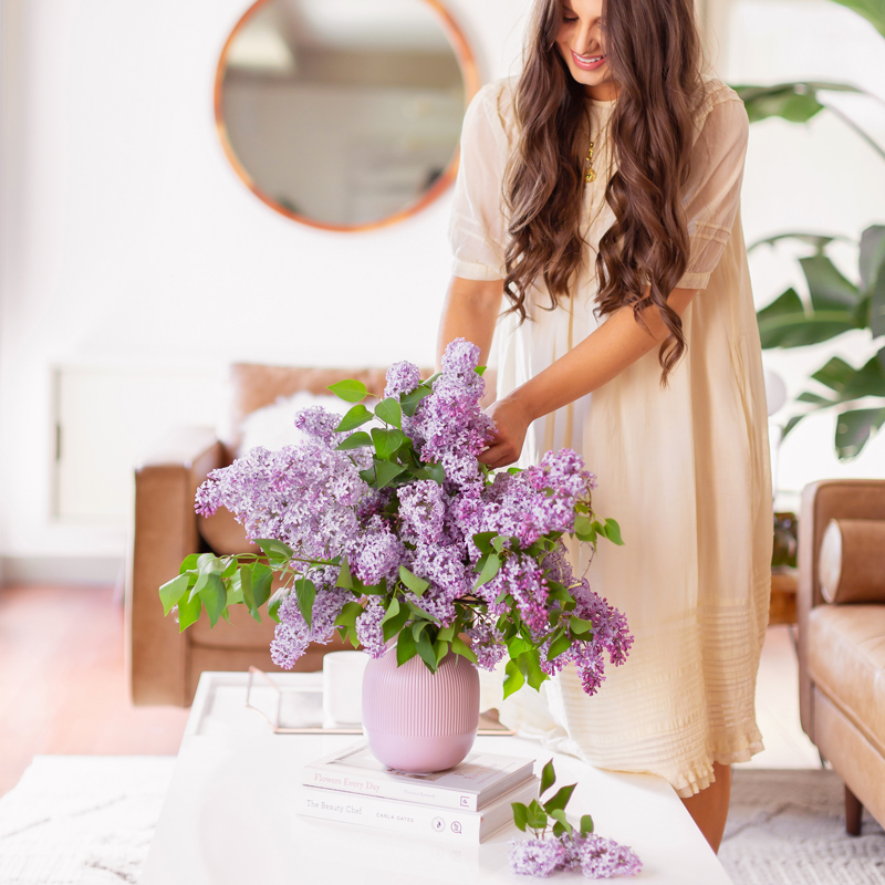June 2019 Soundtrack | Smiling brunette woman in a flowy linen dress creating an oversized lilac arrangement in her mid century modern living room // JustineCelina.com
