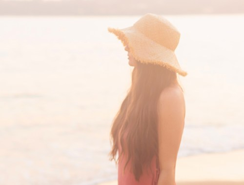 January 2020 Soundtrack | Brunette woman overlooking Tangolunda Bay at Sunset wearing a frayed brim straw hat and a coral dress | Camino Real Zaashila, Huatulco Review | Camino Real Resort Huatulco 2020 | Tangolunda Bay | Calgary Lifestyle, Fashion & Travel Blogger // JustineCelina.com