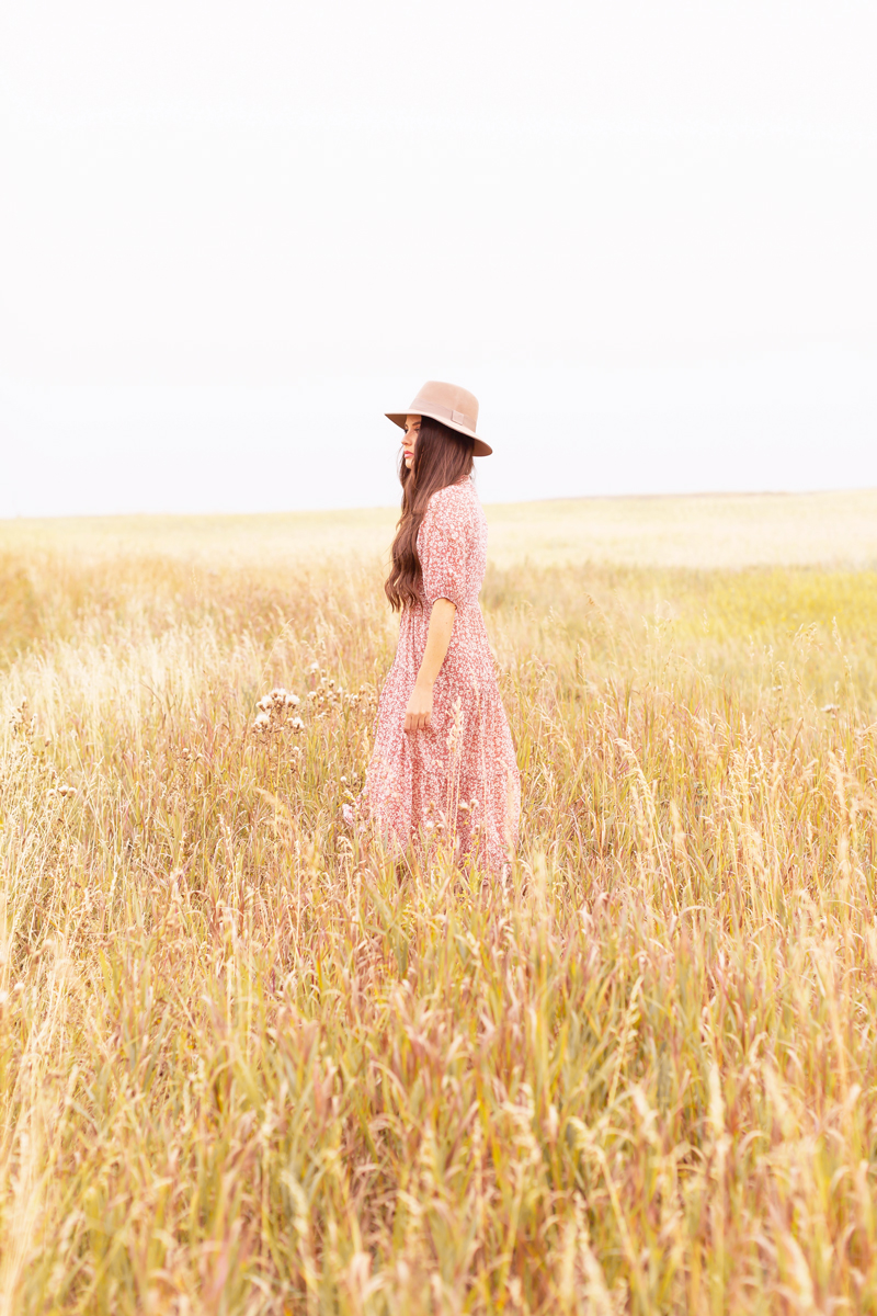 Early Autumn 2020 Lookbook | Prairie Chic | Brunette woman wearing a rose floral midi dress, a tan felt fedora and a round jute bag in a wheat field | Boho Fall 2020 Outfit Ideas | Top Fall 2020 Trends | Fall on the Alberta Prairies | Thanksgiving Outfit Idea | Bohemian Fall outfit Ideas | The Best H&M Knitwear | The Best New Look Chiffon Dresses | Cottagecore Fall Outfit Ideas | How to Style Summer Dresses Into Fall Calgary Alberta Fashion & Lifestyle Blogger // JustineCelina.com