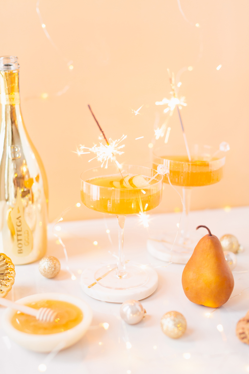 Gilded Vanilla Pear Sparkler   A glitzy, French 75 inspired New Years Eve cocktailfeaturing 24 karat gold infused gin, Bottega Gold Prosecco, Italian vanilla liqueur, lemon juice andHoneyed Vanilla Pear Syrup   Best NYE 2020 cocktails   How to Make sparkling NYE cocktails at home   Champagne cocktail recipe   Champagne Christmas drinks   New Years Eve Sparklers   Refined Sugar Free French 75   NYE Cocktail Party Recipes   Calgary Creative Lifestyle & Cocktail Blogger // JustineCelina.com