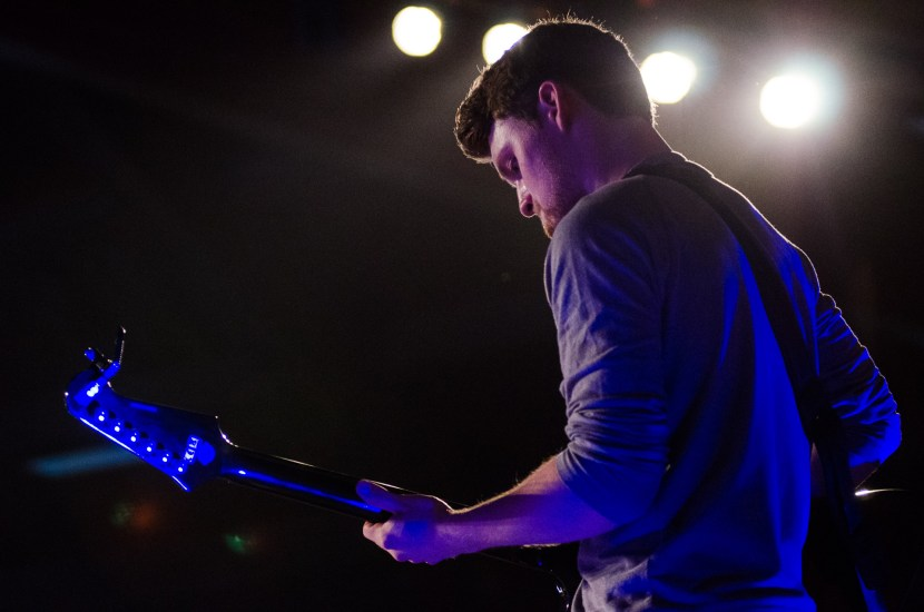 Great shot of a guitarist under the bright lights.