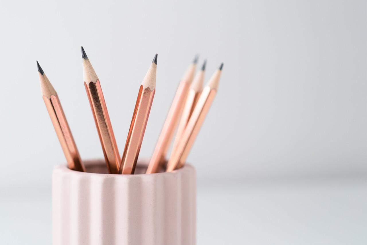 potloden in roze bakje en witte achtergrond