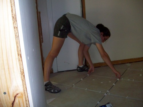 Installing tile over the brand new floor joists, subfloor, and Hardibacker in the kitchen.